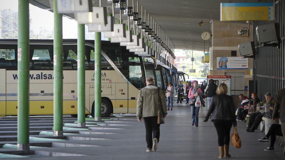 Un grupo de pasajeros consulta los vuelos en el Aeropuerto de Asturias.entrenamiento sporting