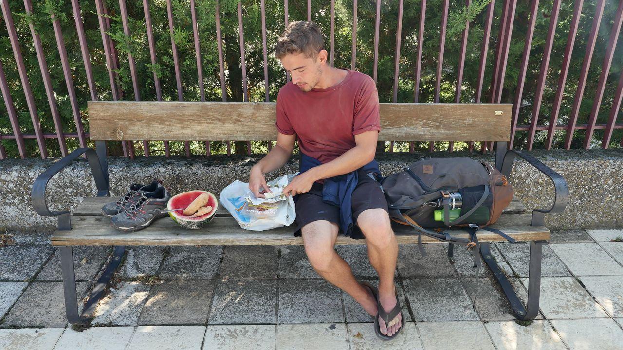 Greg Buda, peregrino húngaro que vive en Dinamarca, despliega sus alimentos a mediodía sobre un banco