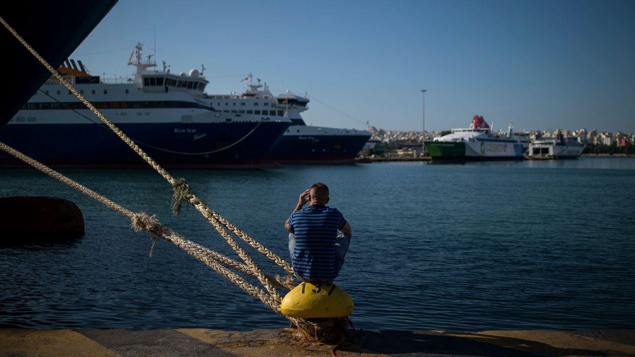 Un hombre se sienta en un bote de amarre frente a los transbordadores atracados en el puerto de El Pireo, en Grecia, durante la segunda huelga consecutiva de 24 horas de las tripulaciones de los transbordadores
