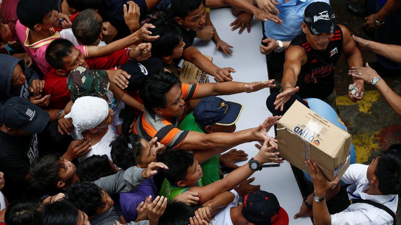 Residentes afectados por las inundaciones se agolpan para recibir ayuda humanitaria en un centro de evacuación en Manila, Filipinas