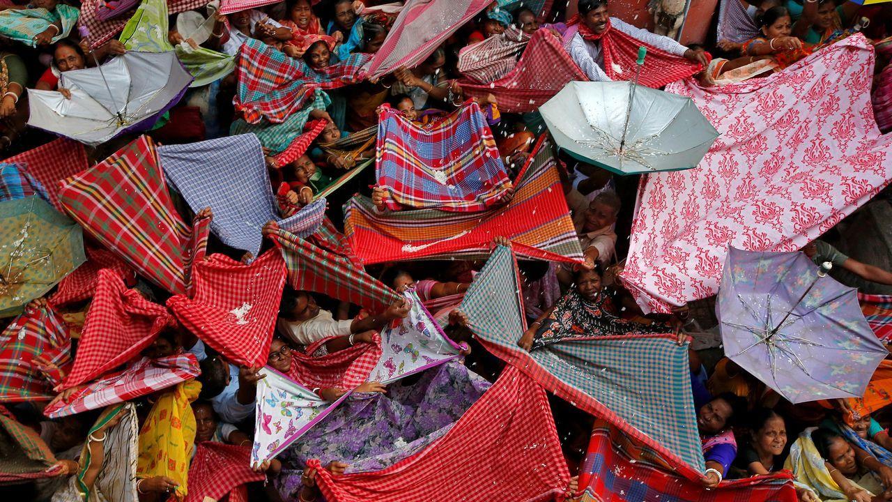 Devotos hindúes extienden ropas y paraguas para recibir arroz distribuido por las autoridades del templo con motivo del festival Annakut en Calcuta (India)