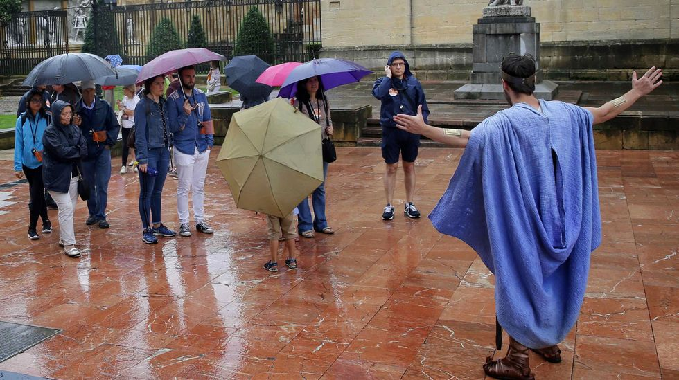 Un grupo de turistas durante una visita guiada por un actor en el entorno de la catedral de Oviedo en un día en el que la Agencia Estatal de Meteorología (AEMET) prevé para hoy en Asturias cielos cubiertos, con bancos de niebla matinales, y lluvias y chubascos acompañados de tormentas, que serán más intensos y frecuentes en Cordillera y Picos de Europa
