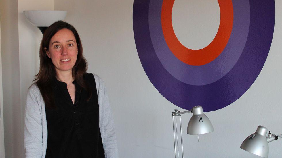 Laura Viñuela, en su despacho, junto a logo de Espora, su empresa