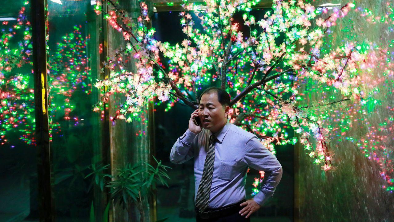 Un hombre hablando por telefono en un restaurante de Corea del Norte.