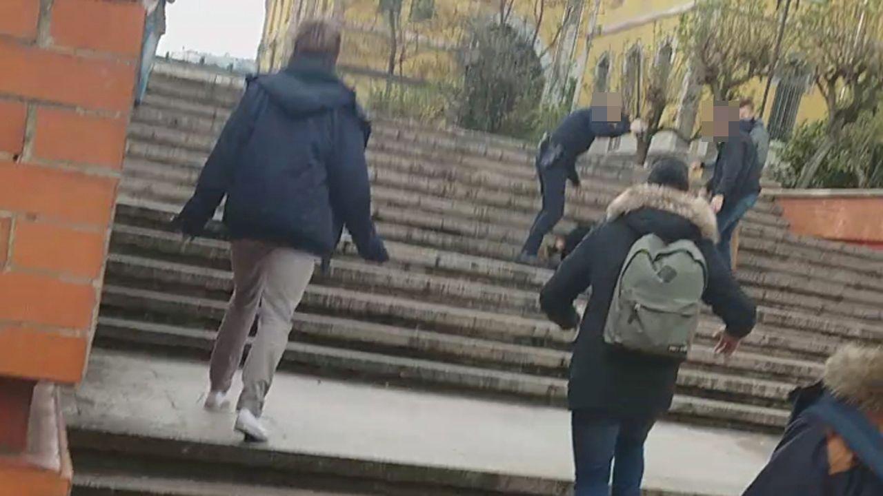 Un policía agrede con un tolete a una persona tirada en el suelo, ante la mirada de una segunda persona y varios universitarios que se les acercan