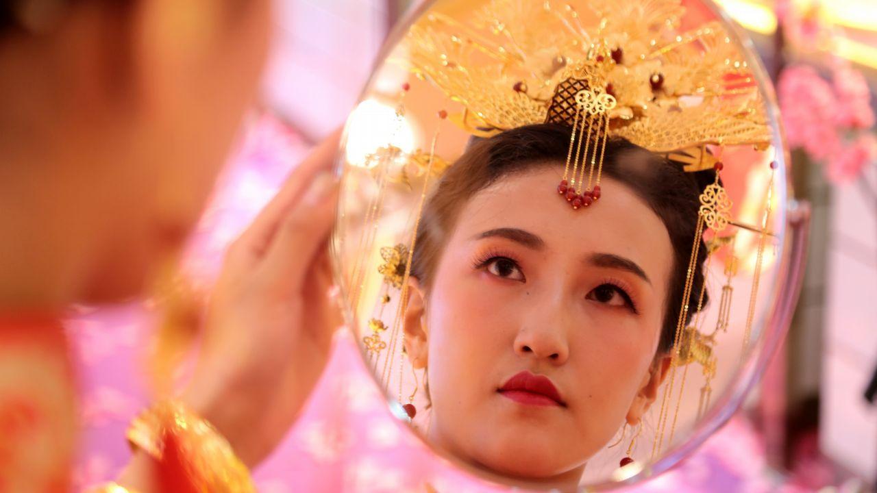 Una modelo china se mira al espejo luciendo un atuendo de novia quie lleva accesorios de oro. El modelo cuesta más de cinco millones de yuanes, es decir 724.973 dólares
