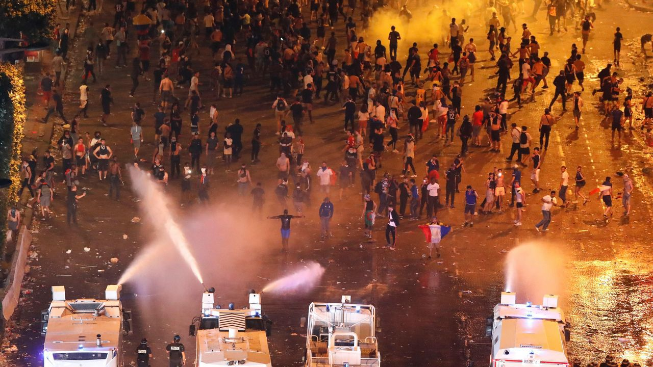 Agentes antidisturbios disparan agua para dispersar a los alborotadores tras el partido entre Francia y Croacia