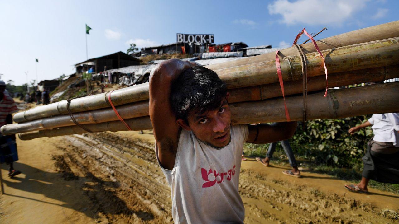 Un hombre carga con bambú en el campamento de refugiados de Jamtoli en Blangladesh
