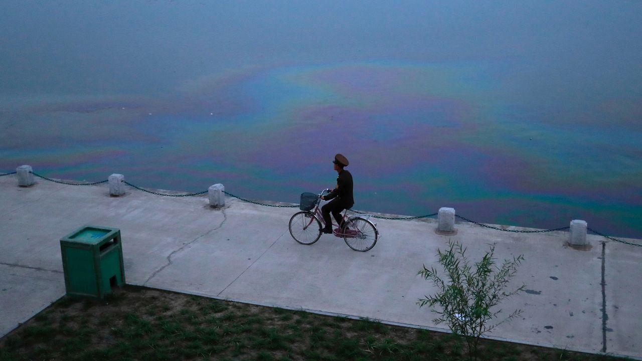 Un soldado pasea en bicicleta por el paseo que rodea un río de Pyongyang.