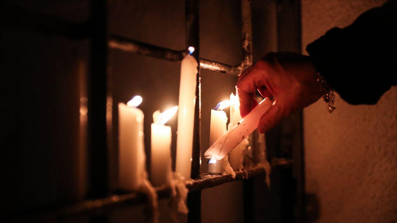 Una mujer enciende varias velas para honrar a los detenidos o desaparecidos durante la dictadura militar de Augusto Pinochet hoy, martes 11 de septiembre de 2018, a las afueras del Estadio Nacional de Santiago de Chile.