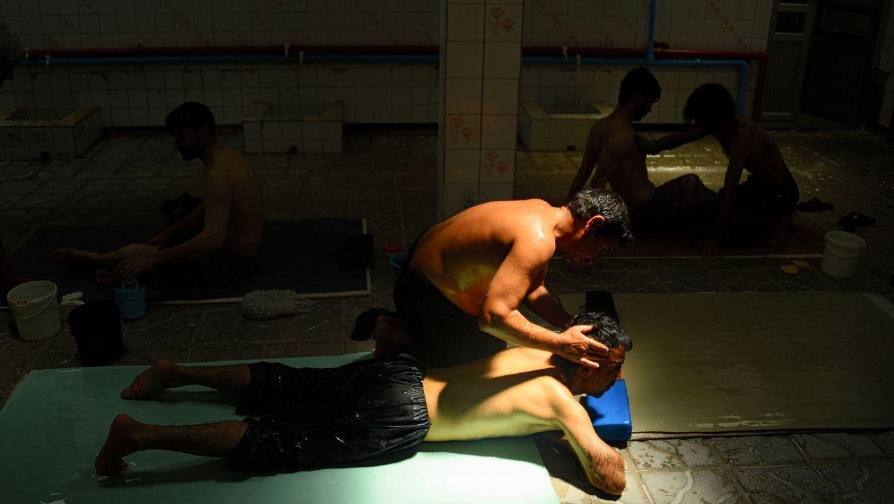 Un hombre afgano recibe un masaje en unos baños públicos de Herat, en Afganistán