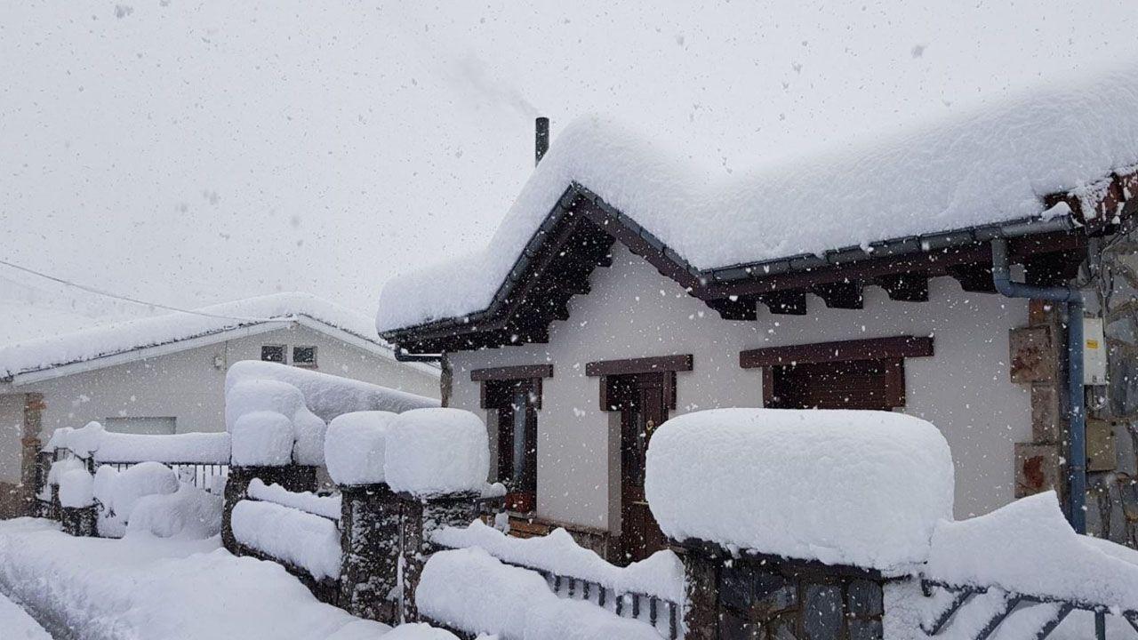 Las casas del pueblo de Pajares con los tejados y las verjas cubiertas de nieve