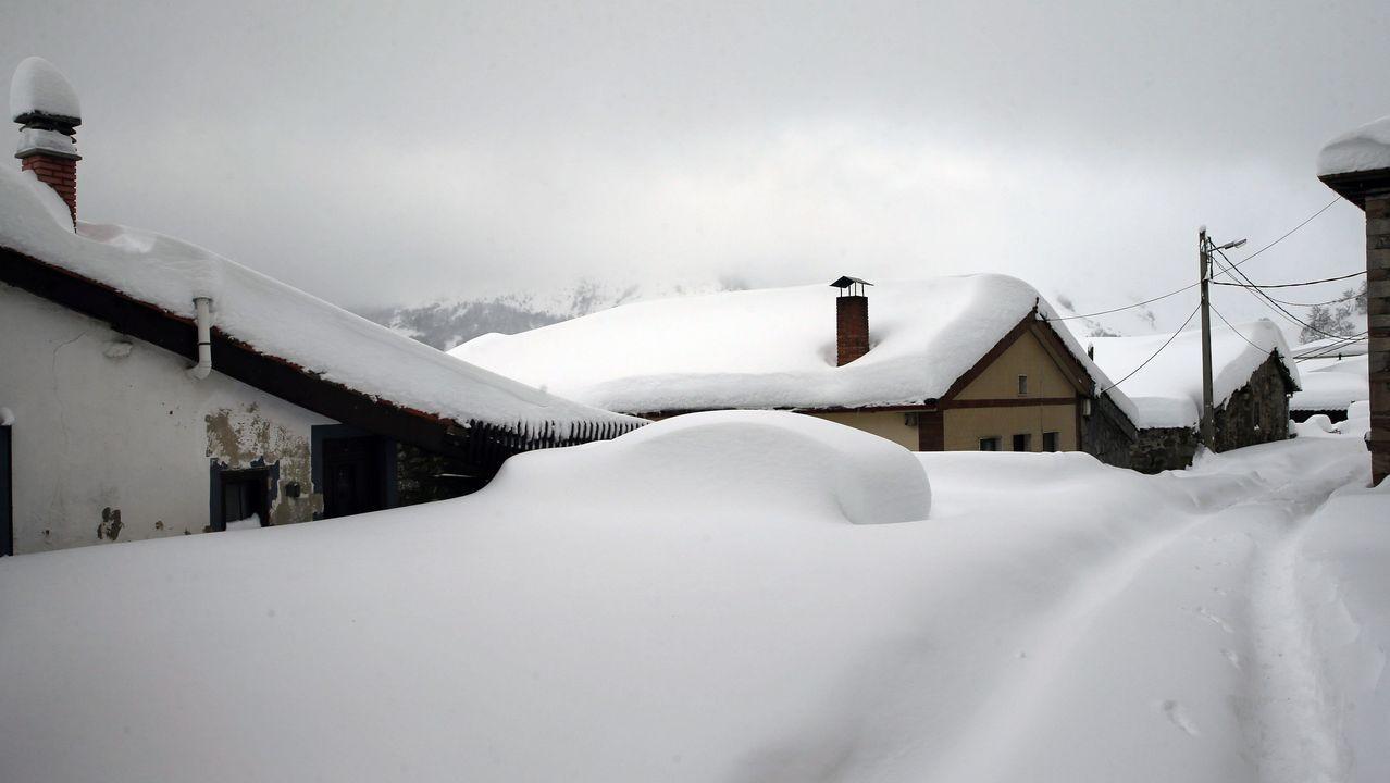 .Un vehículo cubierto de nieve, en el pueblo asturiano de Pajares