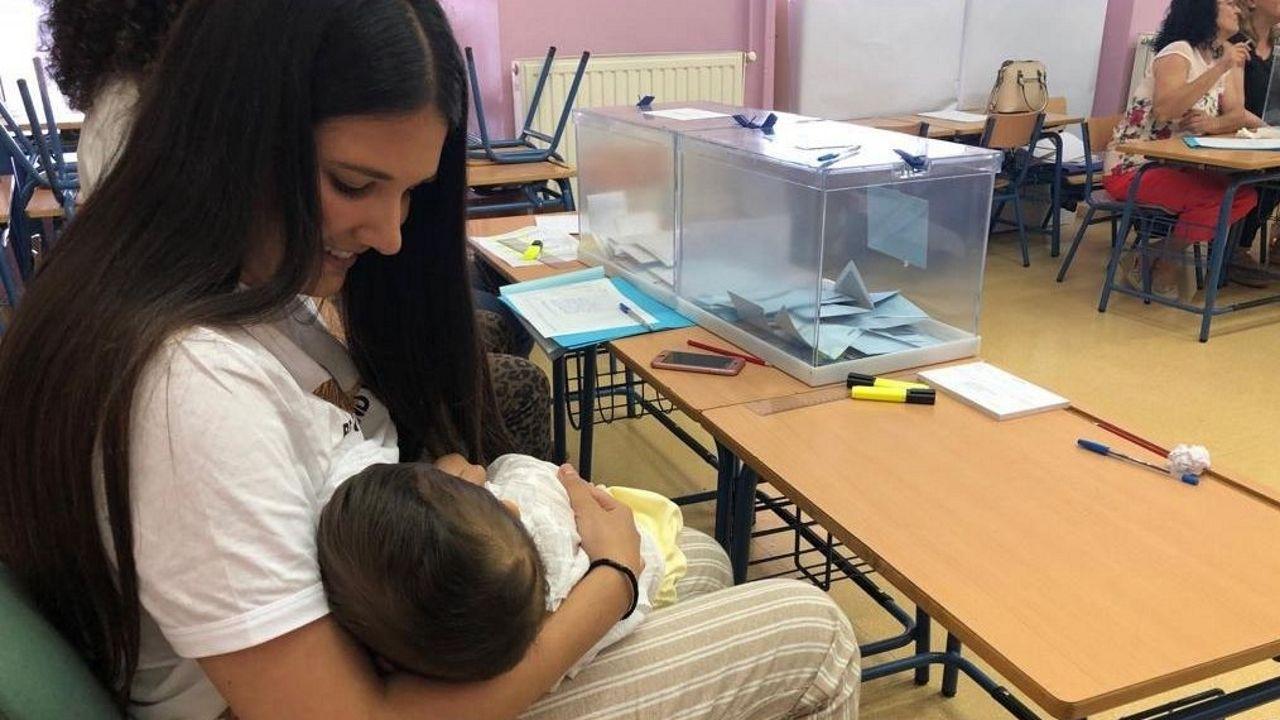 La presidenta de una mesa electoral de Arahal (Sevilla) amamanta a su hijo durante la votación