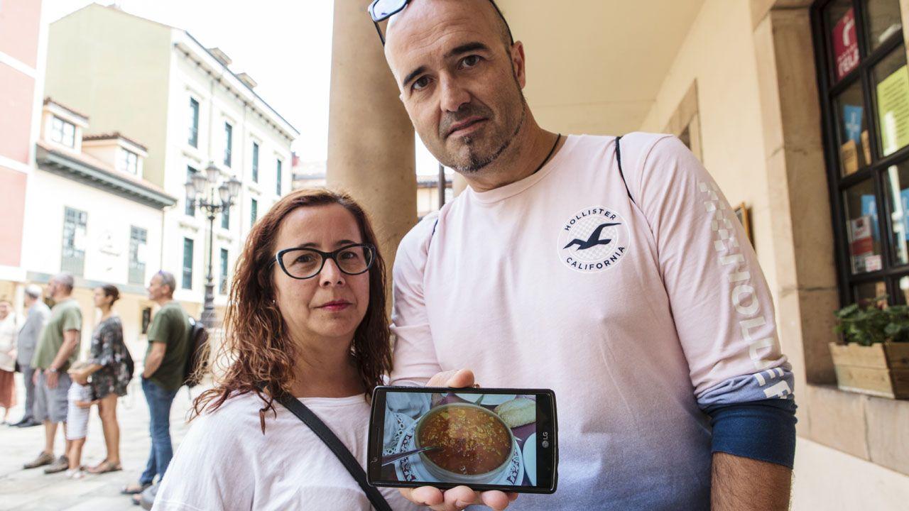 Turistas que pasean por Oviedo muestran una foto de uno de los platos que más han disfrutado durante sus vacaciones por Asturias: los callos