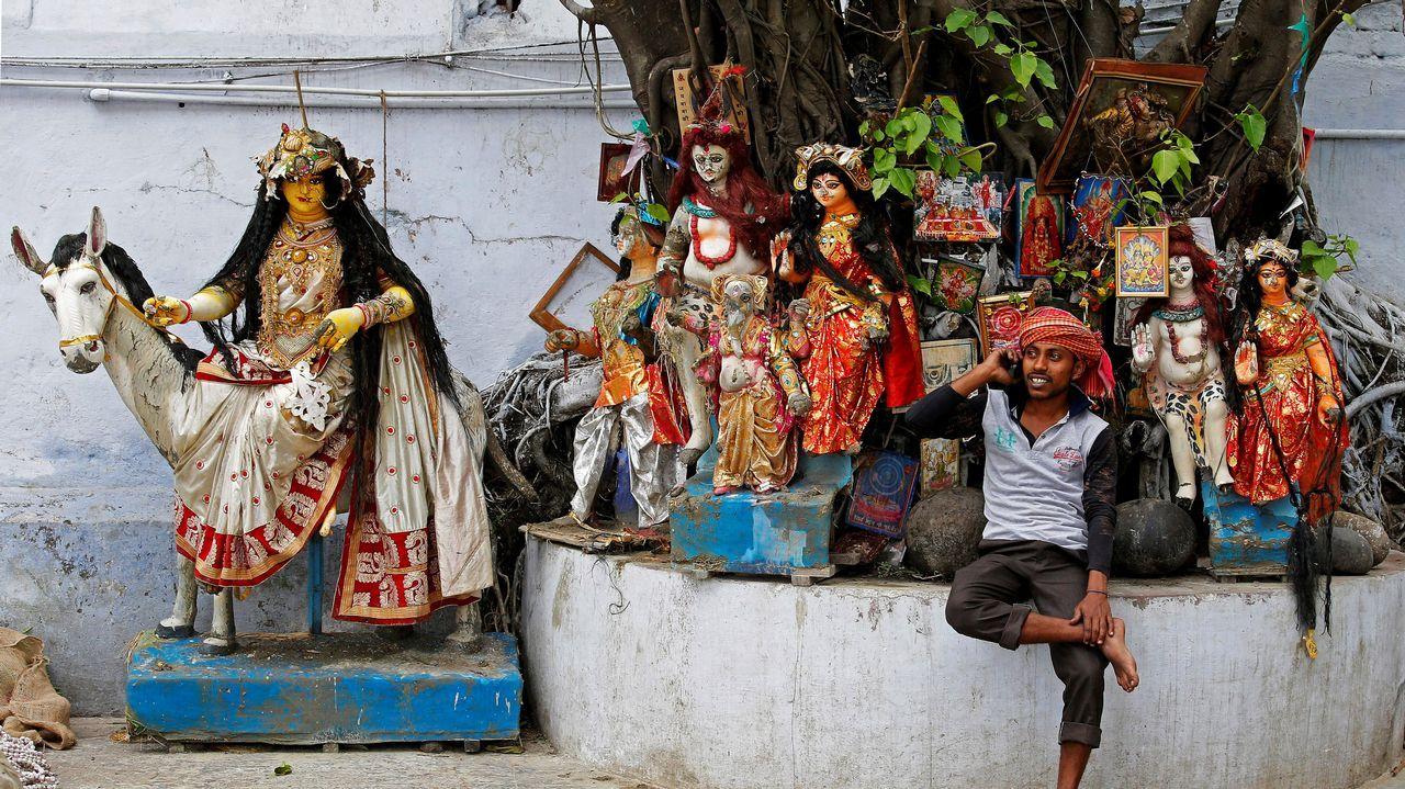 Un trabajador habla con su teléfono móvil junto a varias imágenes de ídolos de Hindu