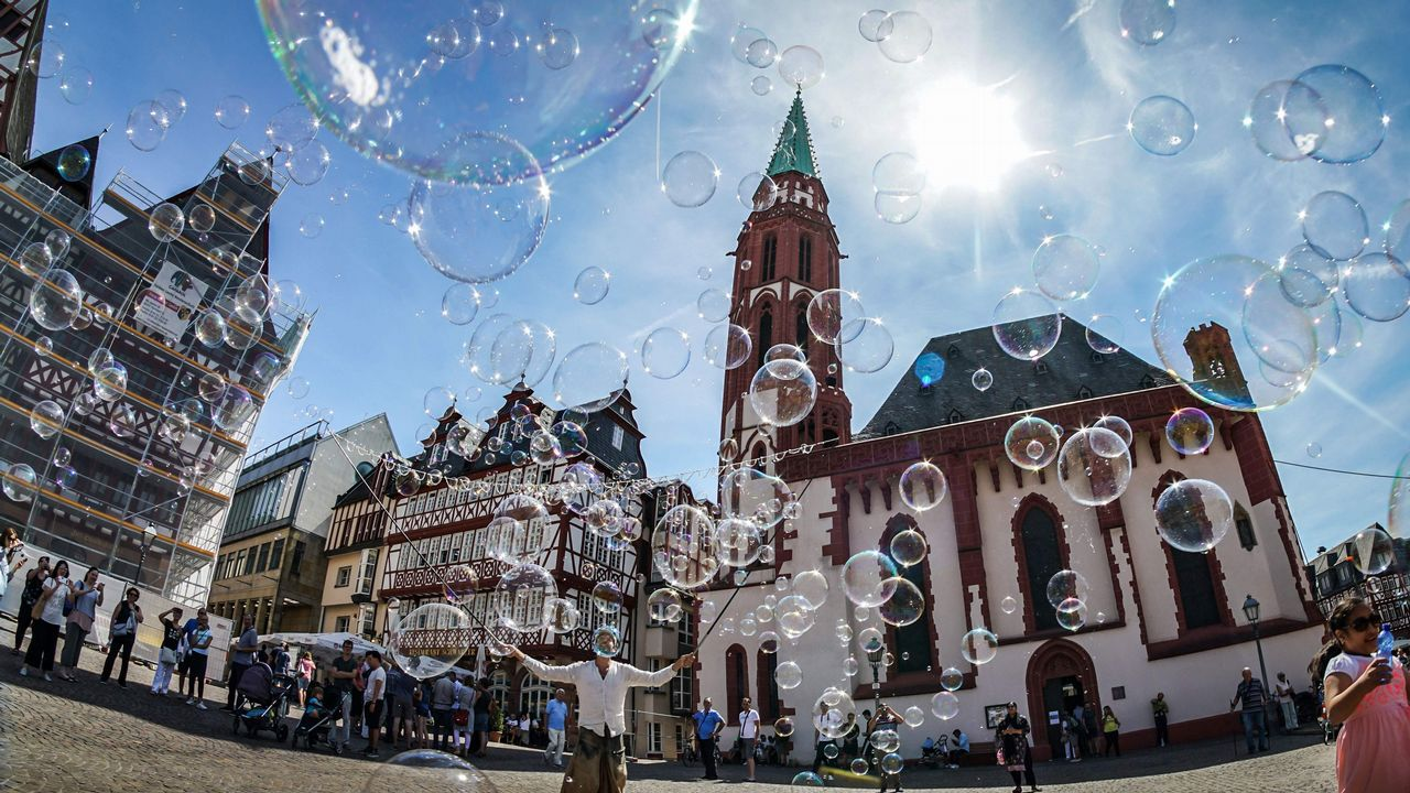 Un artista callejero hace pompas de jabón frente a la iglesia Alte Nikolaikirche en la plaza Roemerberg en Frankfurt am Main, Alemania occidental