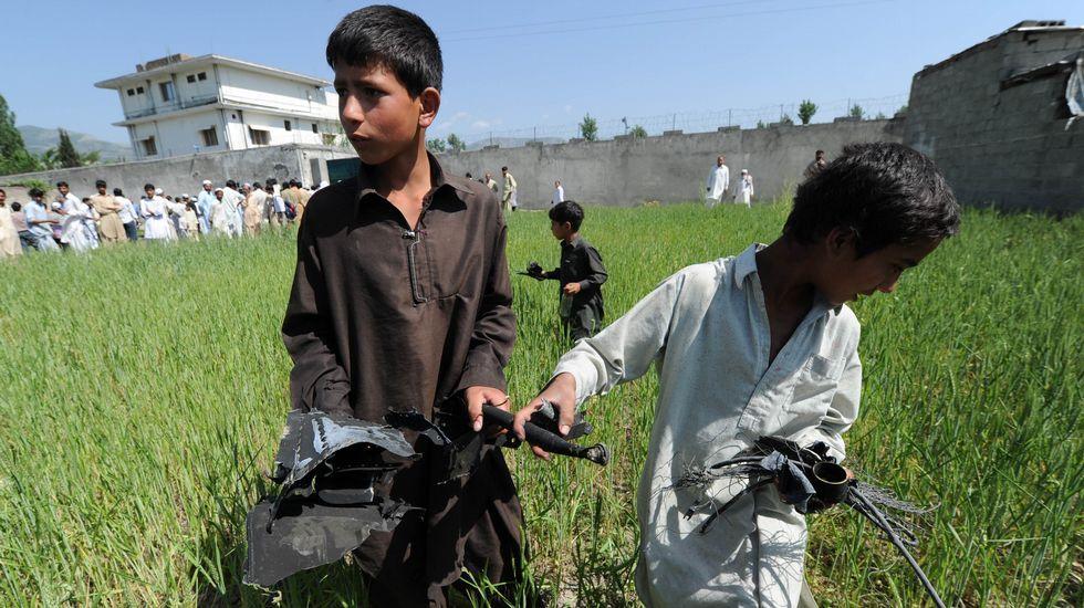 .Fotografía tomada el 3 de mayo del 2011. Un grupo de niños recoge parte de las piezas del helicóptero estadounidense que participó en la operación que acabó con la vida del autor intelectual del 11-S.
