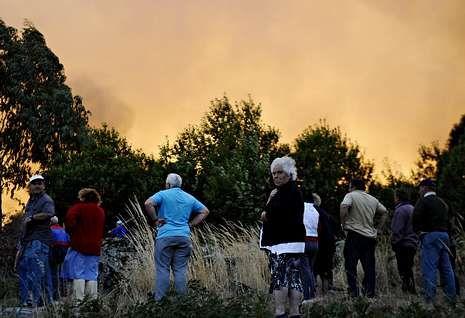 Vecinos de San Martiño (Cualedro) contemplan el gran incendio de la semana pasada.
