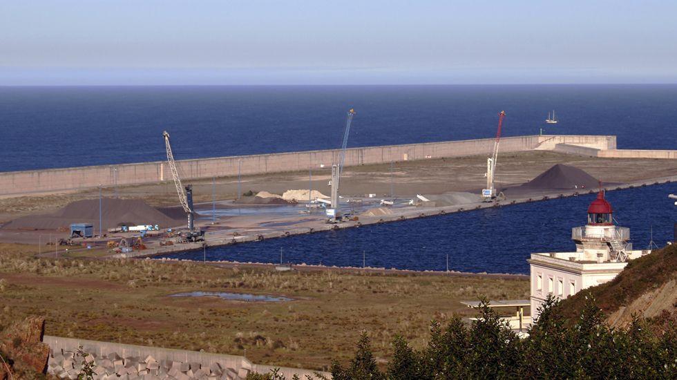 El buque Alonso de Chaves, de Salvamento Marítimo de Gijón.Campa Torres. Un montón de clínker descubierto en el dique de la ampliación. El clínker es el montón gris grande que se ve a la derecha