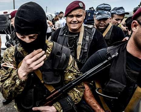 .Un grupo de insurgentes bloquean el camino de acceso al lugar donde cayó el avión.