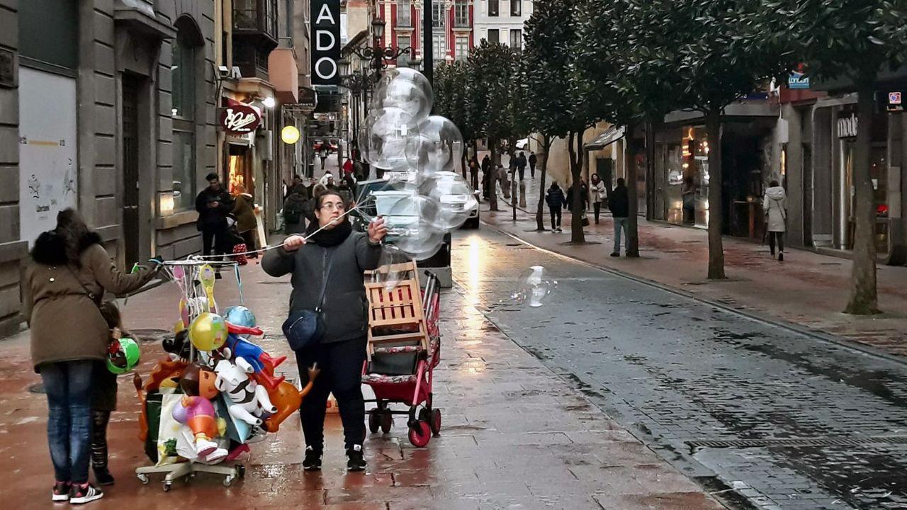 Una vendedora sujeta los globos arrastrados por el temporal de viento, en Oviedo.Una vendedora sujeta los globos arrastrados por el temporal de viento, en Oviedo