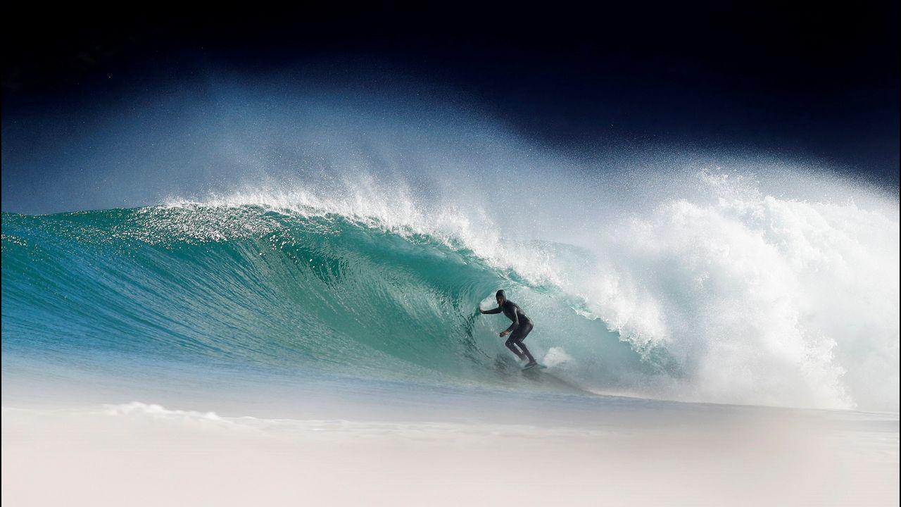 Un surfista monta una ola en el parque nacional Montaña de la Mesa, en Ciudad del Cabo (Sudáfrica)