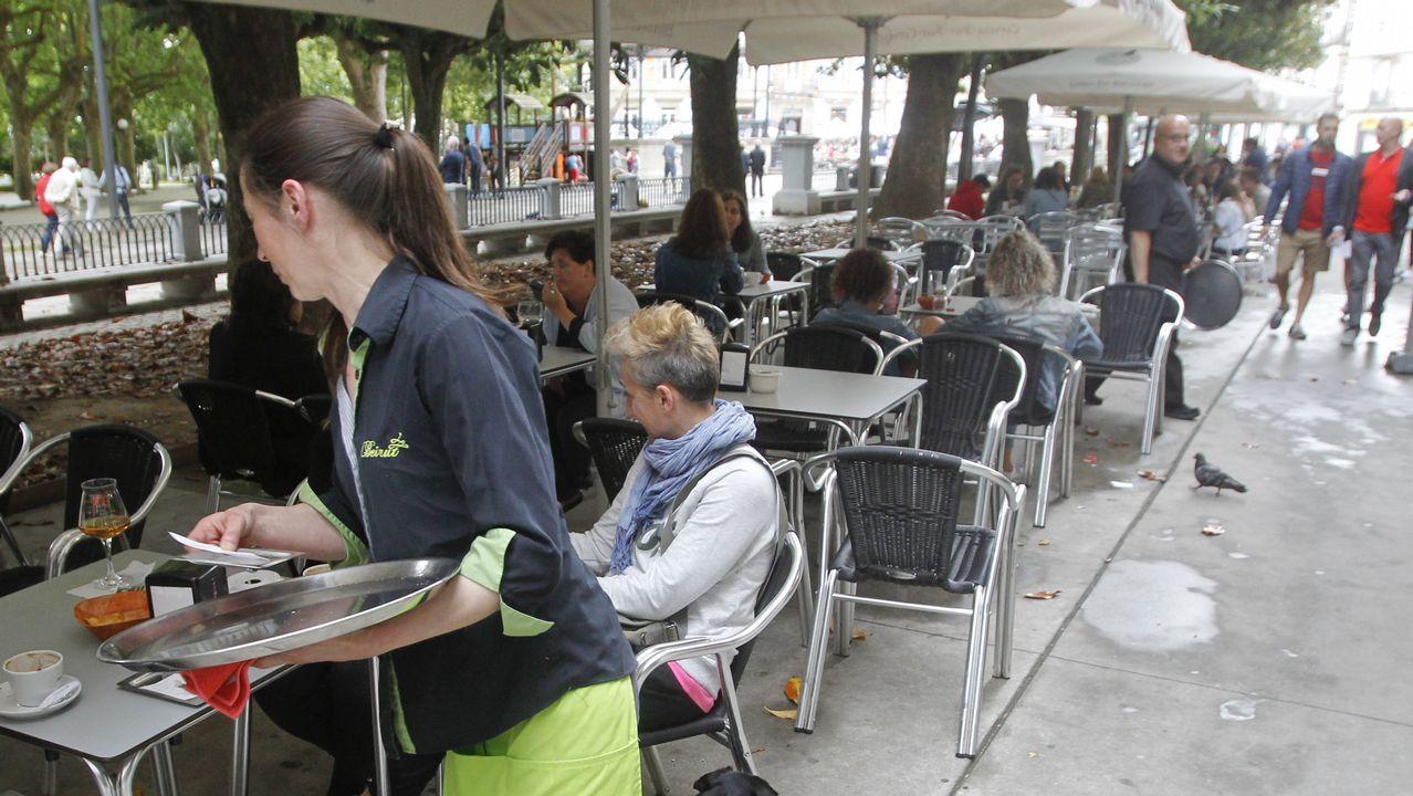 El conselleiro Francisco Conde acude a una demostración en Urovesa.Una camarera trabaja en una terraza de Ferrol