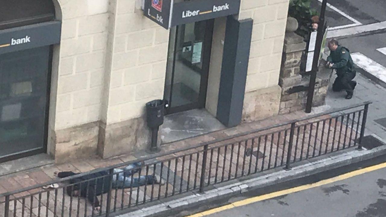Uno de los atracadores de Cangas de Onís boca abajo en la acera delante de la oficina de Liberbank.Uno de los atracadores de Cangas de Onís boca abajo en la acera delante de la oficina de Liberbank