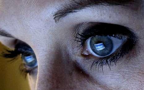 La página de Facebook se refleja en las pupilas de una mujer frente a su ordenador.