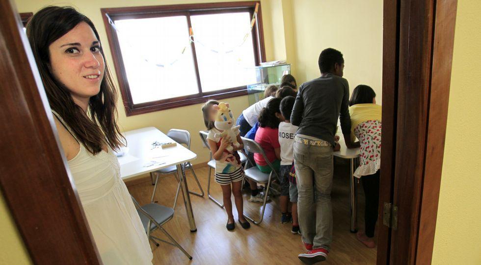 La responsable, Ana Losada, con los niños al fondo, en la oficina de la calle Pino donde tienen lugar las clases de apoyo.