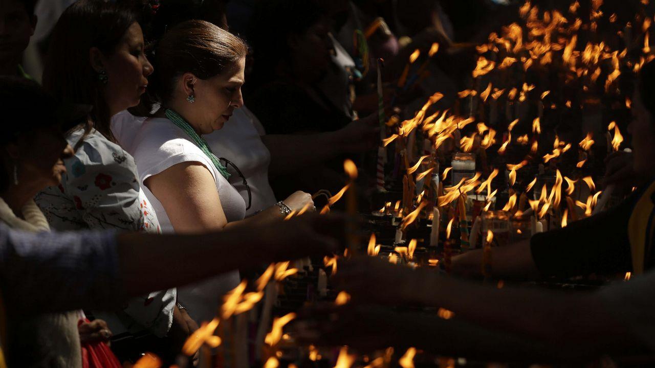 Feligreses catolicos encienden velas en  honor a la virguen de Guadalup en El Salvador