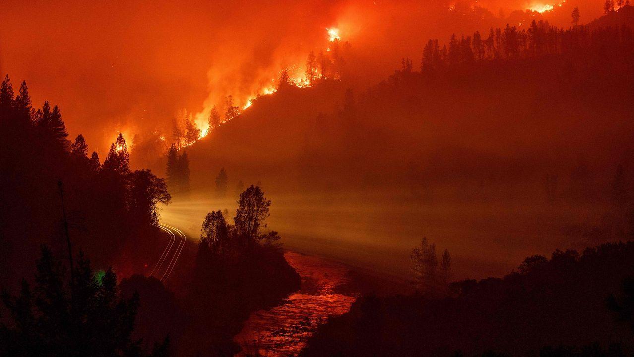 .La luz de un tren procedente de una curva se observa en mitad de un valle cercado por las llamas, junto al río Sacramento, en California