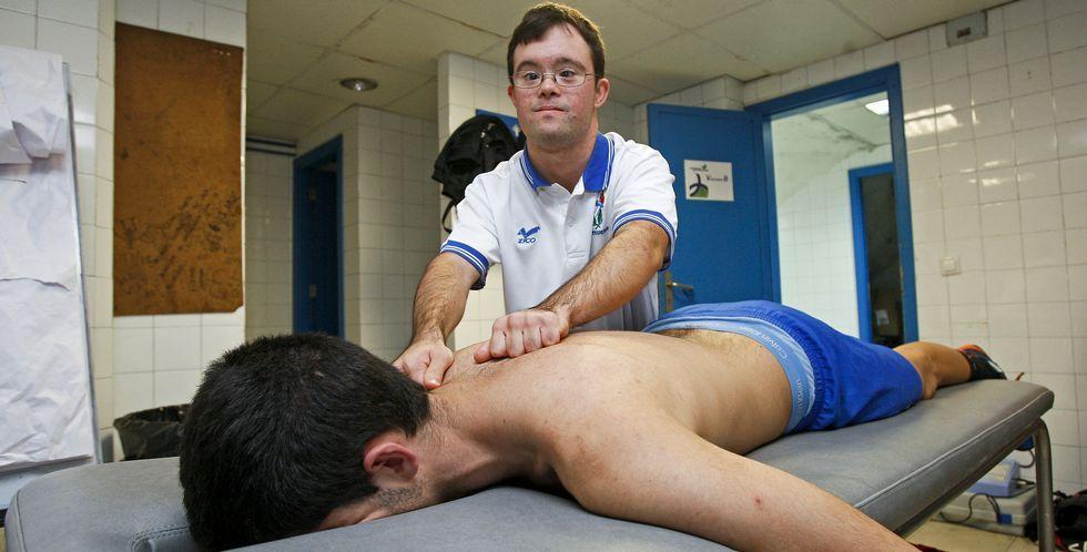 Miguel Pérez da un masaje a un jugador del Teucro antes del entrenamiento de ayer en el pabellón municipal.