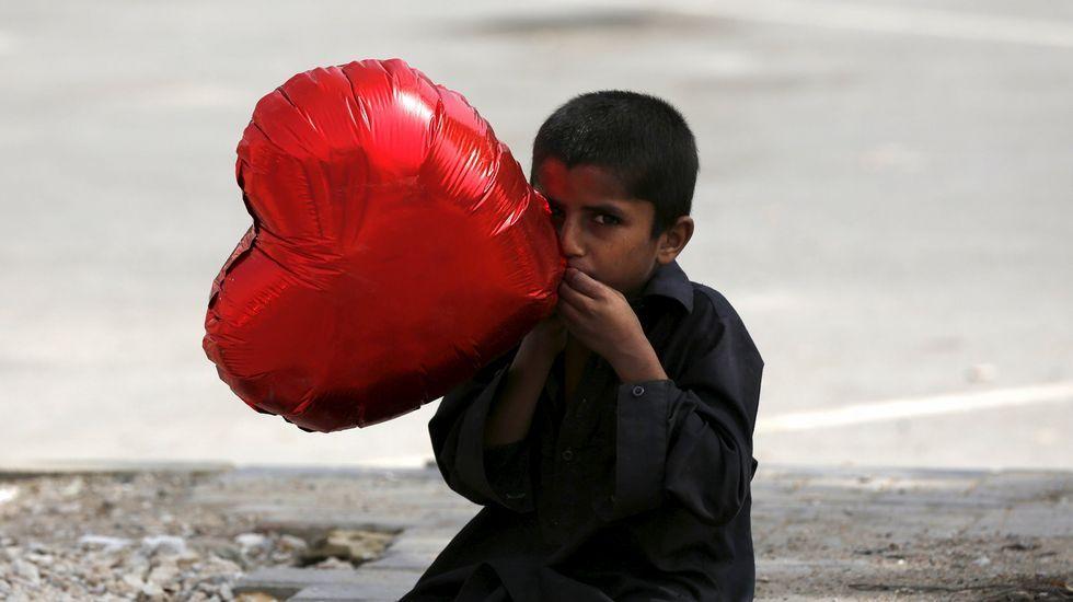 Un niño hincha un globo con forma de corazón en Karachi