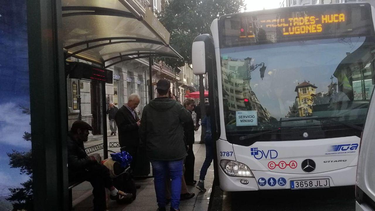 Un autobús de servicios mínimos recoge a varios usuarios en Uría