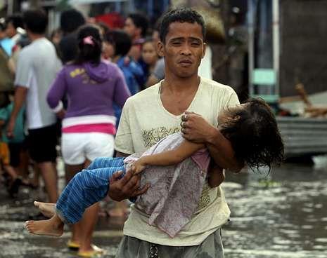 El papa bautiza a la niña de una pareja casada por lo civil.Un hombre lleva a la morgue el cuerpo sin vida de su hija en la ciudad de Tacloban.