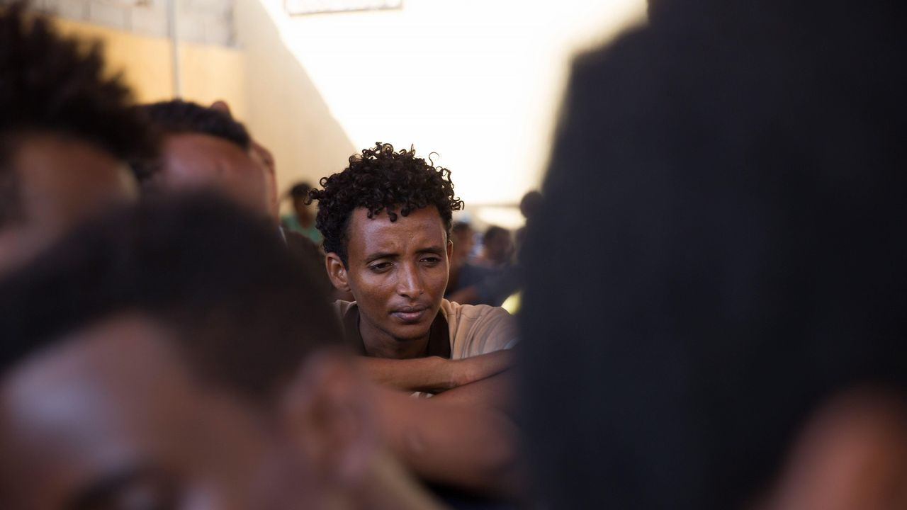 .Migrantes esperan en el centro de detención de Njila después de huir de otro situado junto al aeropuerto debido a las disputas entre las milicias, en Trípoli (Libia)