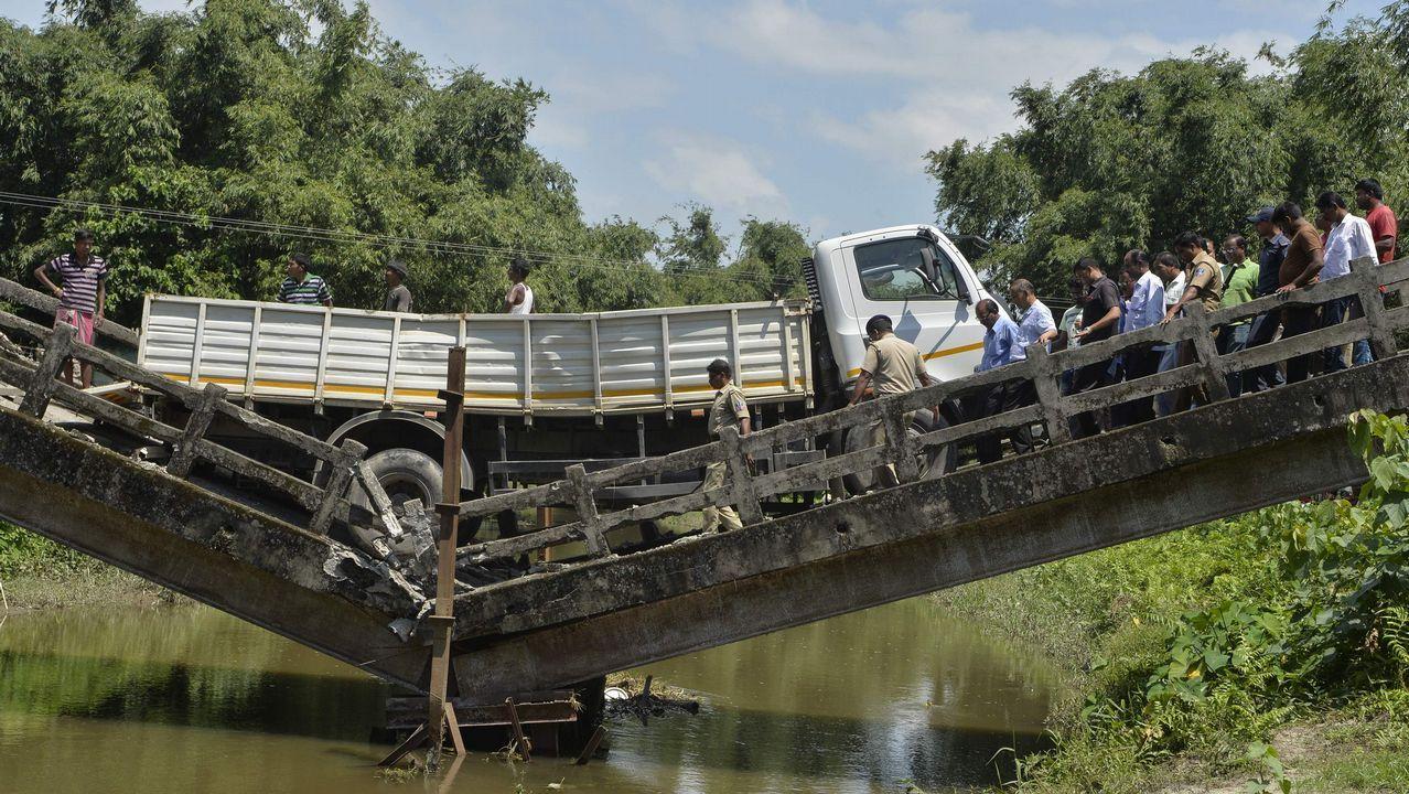 Varios trabajadores indios intentan rescatar un camión atrapado tras el derrumbe de un puente en Siliguri.