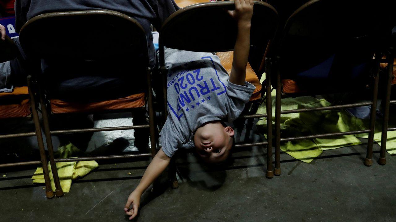 Un niño intenta entretenerse durante uno de los mítines de Trump