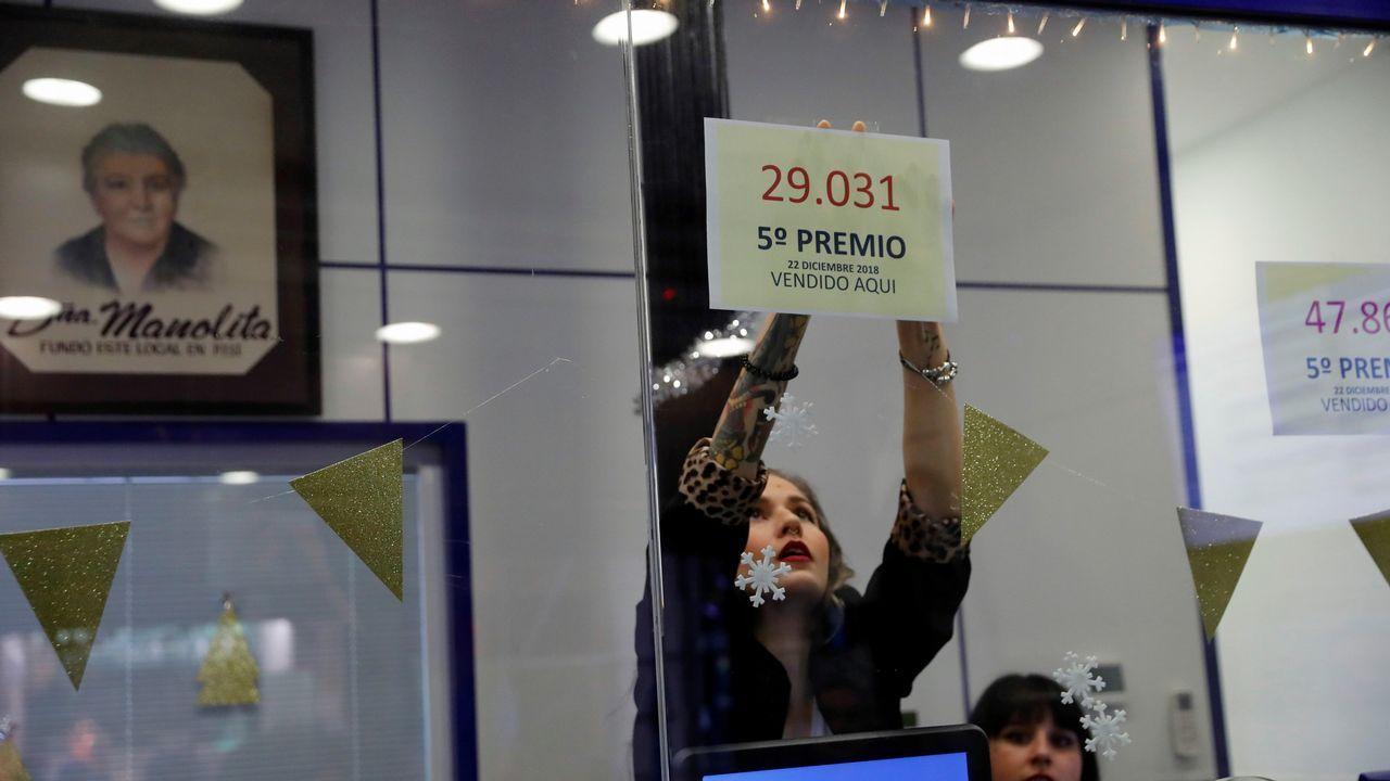 Una empleada de la administración de Loteria de «Doña Manolita», en la madrileña calle Carmen 22, coloca uno los números correspondientes a los tres quintos premios del sorteo Extraordinario de la lotería Navidad dotado con 60.000 euros a la serie cada uno, que ha vendido esta administración.