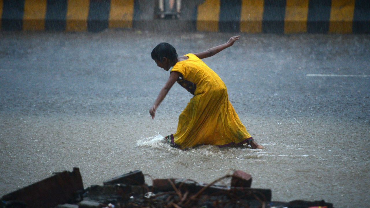 .Una niña camina en una calle inundada de la India