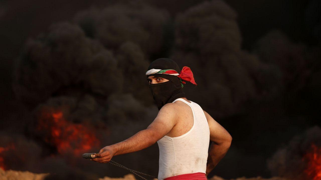 .Un manifestante palestino tira un artefacto contra los policías israelíes en Gaza.