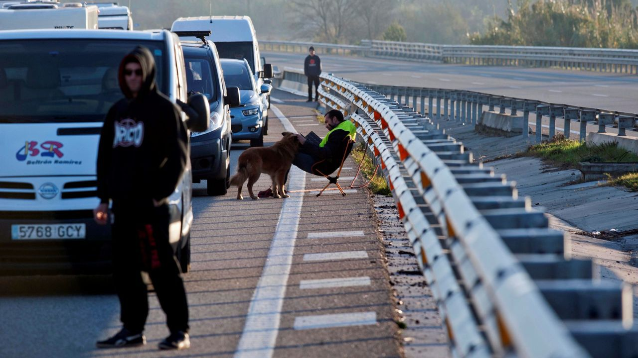 Varios conductores esperan fuera de sus vehículos durante la retención que ha provocado en la autopista AP-7 el corte que han realizado grupos independentistas, en protesta por la reunión del Consejo de Ministros que se celebra en Barcelona