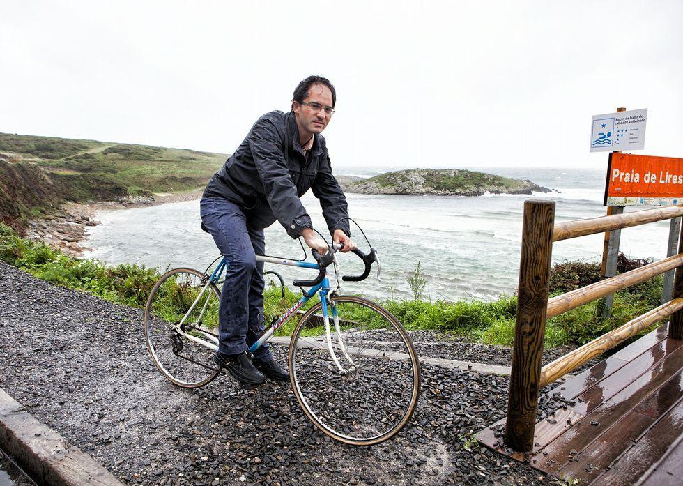 .Fernando Fraga, na praia de Lires, coa bicicleta, noutro día de chuvia de outono de anos despois.