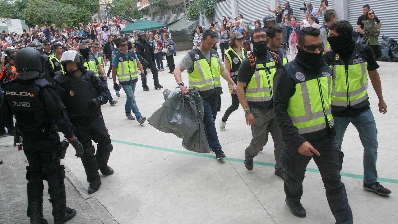 Agentes de la Policía Nacional retiran urnas del IES Tarragona.