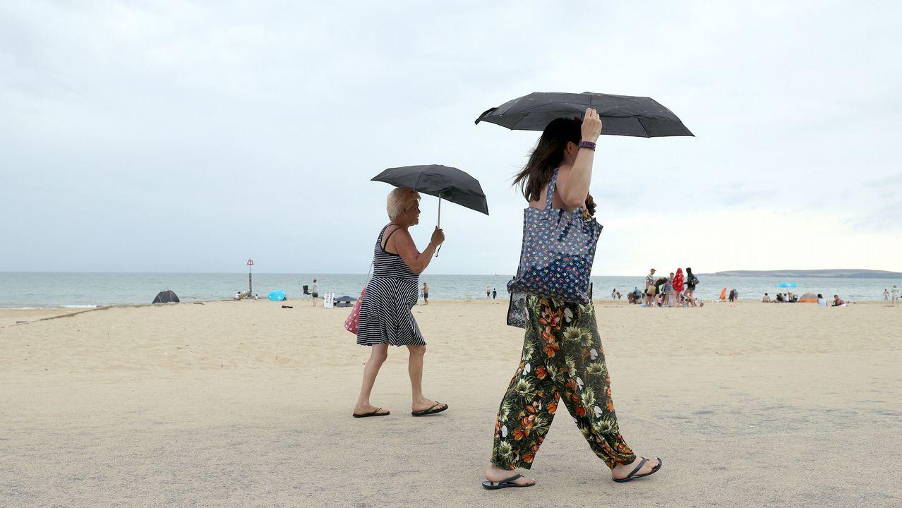 Dos mujeres se protegen del sol con un paraguas en la paya británica de Bournemouth