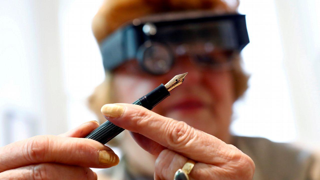 Una mujer inspecciona una pluma de tinta sólida después de repararla en una tienda en Zagreb, Croacia