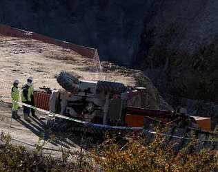 Tres operarios observan la máquina elevadora accidentada ayer en el municipio de Maside