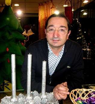 Naya posa, rodeado de adornos navideños, en su tienda de la plaza de Galicia